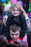 © Joel Goodman - 07973 332324 . 17 November 2013 . Oldham , UK . Happy man with girl on his shoulders in front of the stage . The Christmas lights are turned on in Oldham Town Centre . Photo credit : Joel Goodman