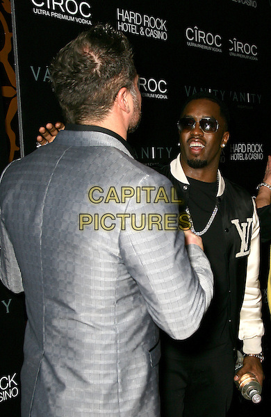 "JASON GIAMBI & SEAN ""DIDDY"" COMBS.grand opening of Vanity Nightclub at Hard Rock Hotel and Casino, Las Vegas, Nevada, USA, .2nd January 2010..half length goatee facial hair earring sunglasses cross necklace black  white jacket silver grey gray back rear behind .CAP/ADM/MJT.©MJT/Admedia/Capital Pictures"