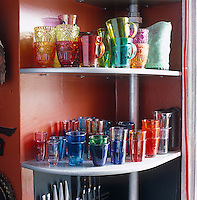 A collection of coloured glassware is stacked on open shelves in the kitchen