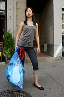 Montreal (Qc) CANADA, July 24, 2007 - Model Released photo- A young asian woman carrries a recycling blue bag outside , on Notre-Dame street in Old-Montreal,a fter the city decide to swith from bins to bags for its curbside recycling collect.<br />