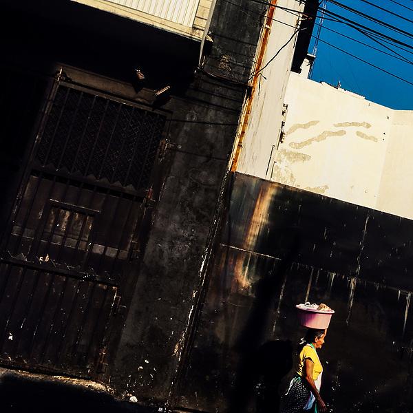 A Salvadoran street vendor, carrying a plastic wash basin on her head, walks in front of an industrial building in San Salvador, El Salvador, 6 April 2018.