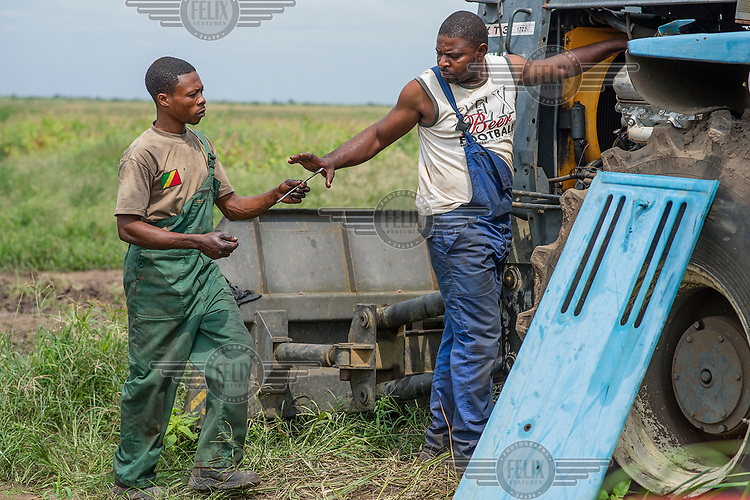 Farm workers maintain a tractor's engine.