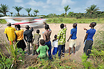Children watching a United Methodist mission airplane taking off.