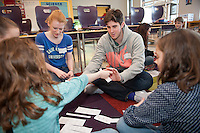 Salve Regina volunteer Jake Williams, '15, and Cathryn Blair,'18, works with children on language skills at the Pell School in Newport as part of a Modern Languages Program.