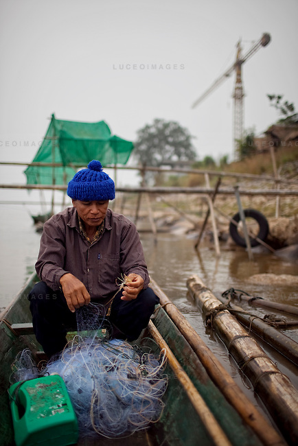 "Mon, 62, pulls a single shrimp from his fishing net that took him nearly two hours to set up. He has been a fisherman for 10 years on the Mekong River in Sop Ruak, Thailand. He says things were better before China built dams and controlled the water level of the river. ""I used to cast my net and catch 10-12 fish now I some times come back with none,"" he said. Photo taken on Thursday, December 10, 2009. Kevin German / Luceo Images"