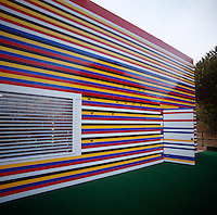 The dramatic multi-coloured striped facade of the Lego house