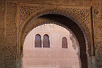 Small horseshoe arch in carved stucco in the portico of the Patio of the Gilded Room, between the Mexuar and the Gilded Room or Cuarto Dorado in the Comares Palace, with intricately carved wall with latticed windows beyond, Alhambra Palace, Granada, Andalusia, Southern Spain. It was built under Mohammed V in the 14th century. The Alhambra was begun in the 11th century as a castle, and in the 13th and 14th centuries served as the royal palace of the Nasrid sultans. The huge complex contains the Alcazaba, Nasrid palaces, gardens and Generalife. Picture by Manuel Cohen