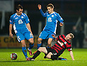 Ayr Utd's Robbie Crawford loses out to Queen of the South's Derek Young and Daniel Carmichael.