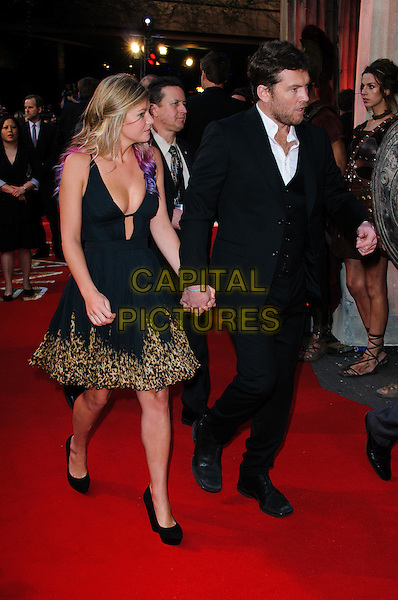 Crystal Humphries & Sam Worthington.'Wrath Of The Titans' European Premiere at The BFI IMAX, London, England..29th March 2012.full length suit dress leopard print trim holding hands profile black white shirt stubble facial hair couple.CAP/CJ.©Chris Joseph/Capital Pictures.