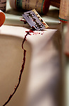 Close-up of razor blade on bathroom sink dripping blood after suicide attempt.
