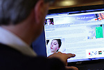 William Massart, left, looks at a website he built for his daughter Sandra Massart, 10, who is being treated for MLD, a degenerative condition, at the family's apartment in Durham, NC, USA, on Tuesday, Feb. 14, 2012.  Photo by Ted Richardson