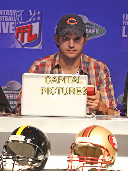 ASHTON KUTCHER. Fantasy Football Superdraft at the Palms Resort Hotel and Casino, Las Vegas, Nevada, USA. .27th August 2010.half length plaid white checked shirt red blue baseball cap hat stubble facial hair apple mac computer laptop .CAP/ADM/MJT.© MJT/AdMedia/Capital Pictures.