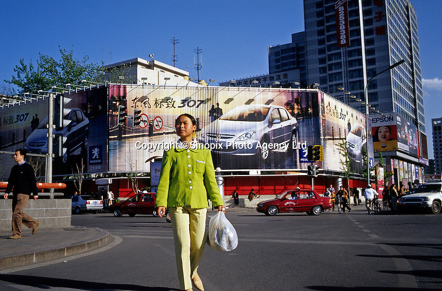 A migrant girl walks past a huge billboard of Peugeot 307 in the street of Beijing, China..25-APR-05