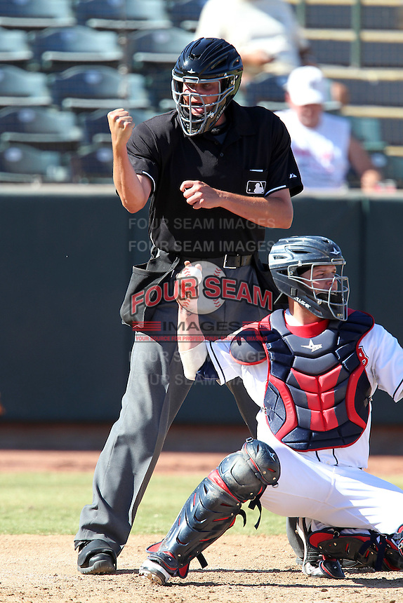 Home plate umpire Jordan Baker makes a call behind catcher Roberto Perez during an Arizona Fall League game between the Phoenix Desert Dogs and Surprise Saguaros at Phoenix Municipal Stadium on October 29, 2011 in Phoenix, Arizona.  Surprise defeated Surprise 11-0.  (Mike Janes/Four Seam Images)