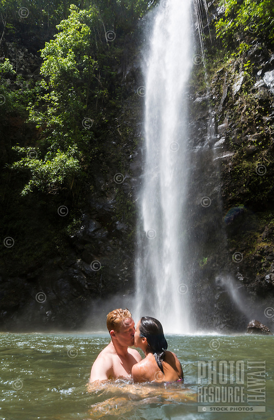 A young couple kiss in the water at Uluwehi Falls, Kaua'i.