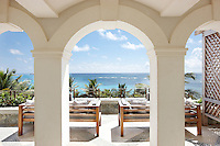 A view through an archway to seating on an outside terrace, whcih gives a view of the sea beyond.