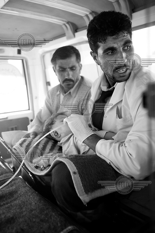 Nurse Said Isa with one year old Satara on his lap in the back of the ambulance, transporting her from a hospital where she had a CT-scan, to another...Kabul Ambulance Service (KAS) is the first such service in Afghanistan. In a country where anyone sick or injured usually is transported to the doctor, or hospital, by taxi, on foot or even on the back of a mule, helped by relatives, an ambulance service equipped with 4WD Landcruisers and nurses is a huge improvement. KAS is currently serving a population of about  4.5 million people with less than 15 ambulances, but hope to expand their services. © Fredrik Naumann