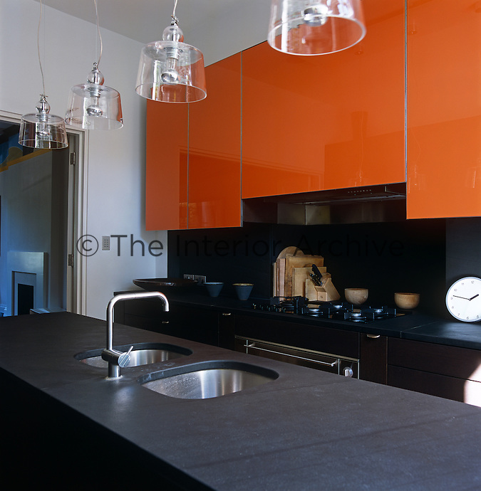This contemporary kitchen has worktops in dark slate and cupboards faced with orange safety glass