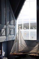 A view through an angular shaped window with a blue shutter giving a view towards Cadaques