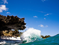 Wave breaking under lava rock ledge at Pounders Beach on the east side of Oahu Hawaii, photographed from the water