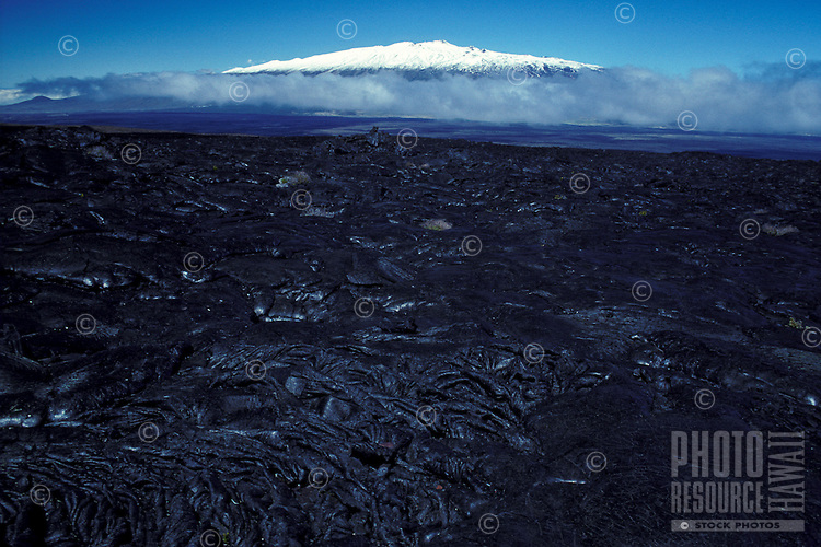 Lava fields of Mauna Loa, with clouds gathering in the saddle between the two volcanoes, and the summit of Mauna Kea in the background