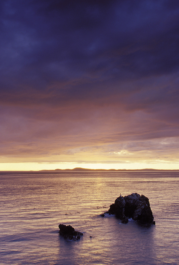 Storm clouds and sunset over Urchin Rocks, Vancouver Island in distance, Deception Pass State Park, Fidalgo Island, Washington