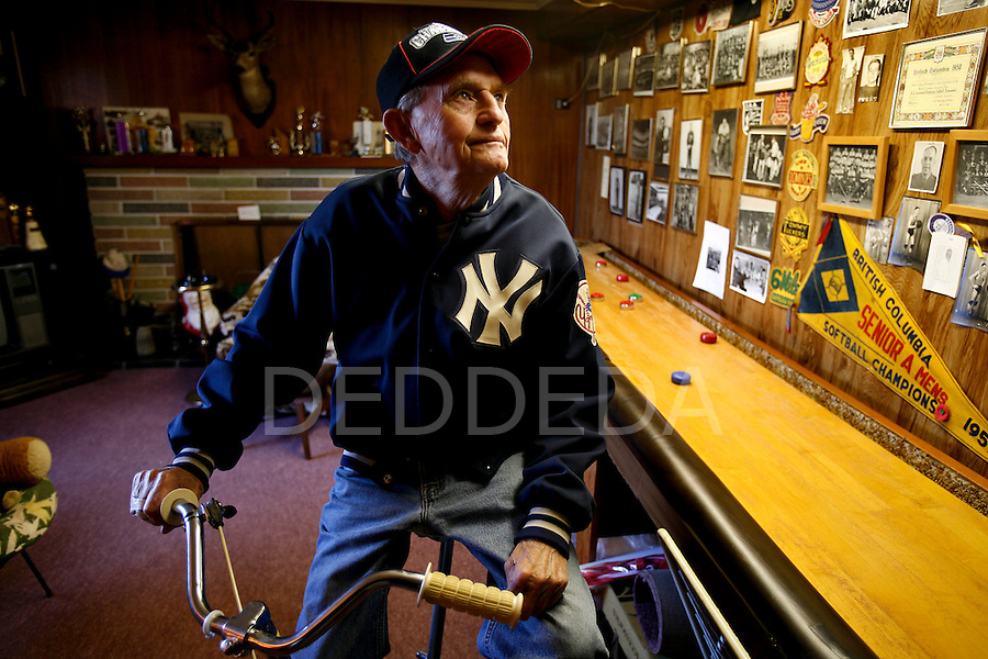 Joe Bryant, 85, looks at his wall plastered with sporting photographs collected over the years from teams he has played on throughout his life, in his basement in Victoria, British Columbia. Bryant is being inducted into the Greater Victoria Sports hall of Fame this weekend for playing such sports as lacrosse, softball, basketball, and badminton. Photo assignment for the Globe and Mail national newspaper in Canada.
