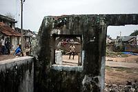 Children plays cricket near a house which was destroyed in 2004 Tsunami. Kichankuppam, Nagapattinam, Tamil Nadu, India.