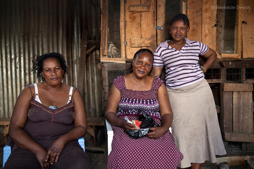 Jane (C), the owner of the Madiaba Busaa Club, with her two sisters Roseline (L) and Mary (R) at the Madiaba Busaa Club in a Nairobi slum on March 27, 2013. Jane has been brewing Busaa for 22 years. She opened the Madiaba Busaa Club in 1991. Busaa is made by crudely fermenting maize, millet, sorghum or molasses. At Kshs 35 per liter it is much cheaper than a Kshs120 half-liter bottle of commercial beer. The local brew was legalised in 2010 and since then busaa clubs have become increasingly popular. Drinking is on the rise in Kenya, especially among young people. Photo: Benedicte Desrus