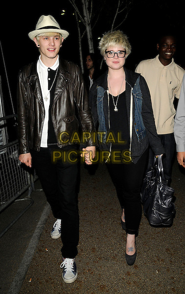 LUKE WORRELL & KELLY OSBOURNE.The Nokia Skate Almighty launch party, Potters Field, Tooley St., London, England..August 5th, 2009.full length black leggings jean denim sleeveless jacket glasses hoodie hooded top grey gray silver bag purse cream beige fedora trilby leather jeans denim couple tattoo holding hands .CAP/CAN.©Can Nguyen/Capital Pictures.