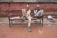 Two man sit on a bench in front of Pashupati Nath temple in Kathmandu, Nepal