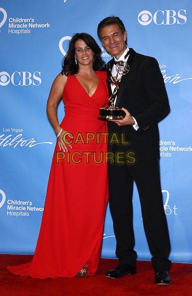 LISA OZ & DR. MEHMET OZ.2011 Daytime Entertainment Emmy Award Press Room at The Las Vegas Hilton, Las Vegas, Nevada, USA..June 19th, 2011.full length award trophy winner  red dress black suit married husband wife.CAP/ADM/MJT.© MJT/AdMedia/Capital Pictures.