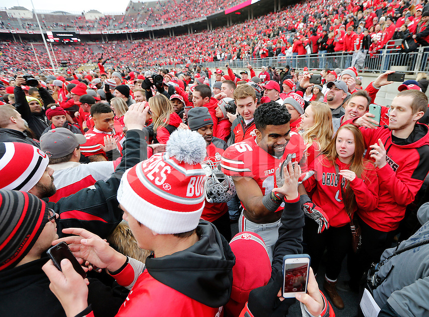 Ohio State Buckeyes running back Ezekiel Elliott (15) high fives fans in a mob of people after the college football game between the Ohio State Buckeyes and the Michigan Wolverines at Ohio Stadium in Columbus, Saturday morning, November 29, 2014. The Ohio State Buckeyes defeated the Michigan Wolverines 42 - 28. (The Columbus Dispatch / Eamon Queeney)