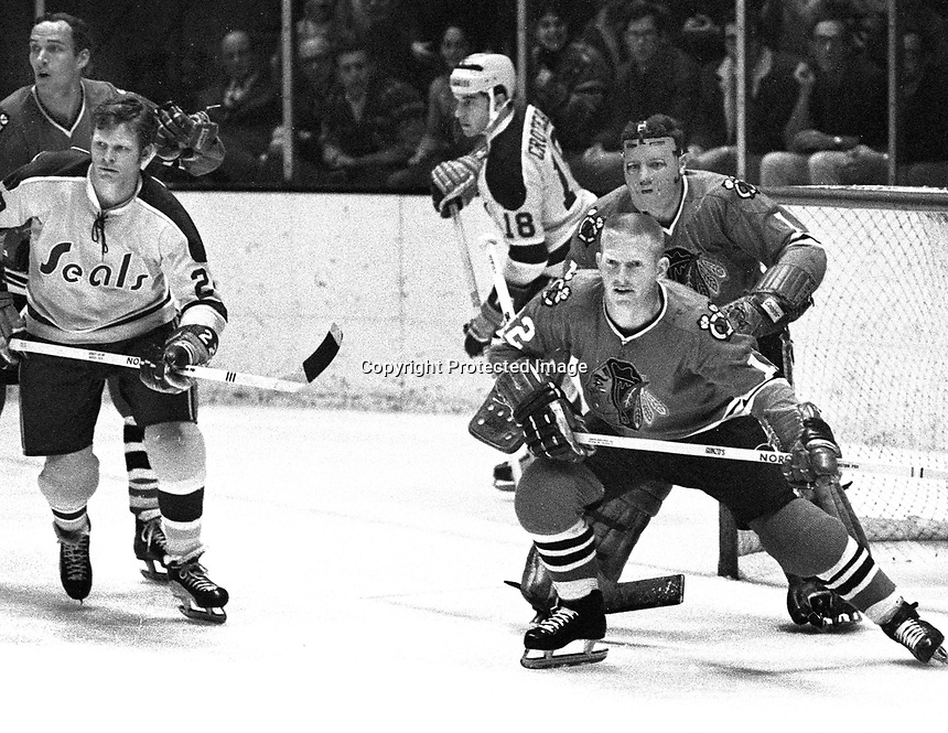 Seals vs Chicago Black Hawks: #22 Dennis Hextall .#18 Gary Croteau, Hawks are Pat Stapleton and goalie Gerry Desjardins..(1970 photo by Ron Riesterer)