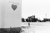 Iraq. Al Khamas. A young muslim boy walks on the road. A heart is drawn on the wall. Arabic writings. © 2003 Didier Ruef