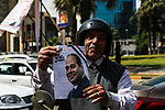An Egyptian man holds privately-sponsored posters of incumbent President Abdel Fattah al-Sisi on the the second day of the presidential election at a polling station, in Cairo, Egypt, on March 27, 2018. Egyptians head to the polls in a three-day vote to choose between incumbent Abdel Fattah al-Sisi and candidate Moussa Mostafa Moussa. Photo by Fayed El-Geziry