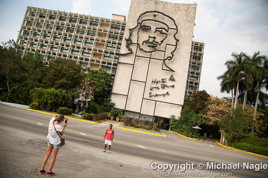 "HAVANA, CUBA -- MARCH 22, 2015:   Tourists pose for pictures in front of Che Guevara's image and slogan ""Hasta la Victoria Siempre"" on the Ministry of the Interior building in the Plaza de la Revolución in Havana, Cuba on March 22, 2015. Photograph by Michael Nagle"