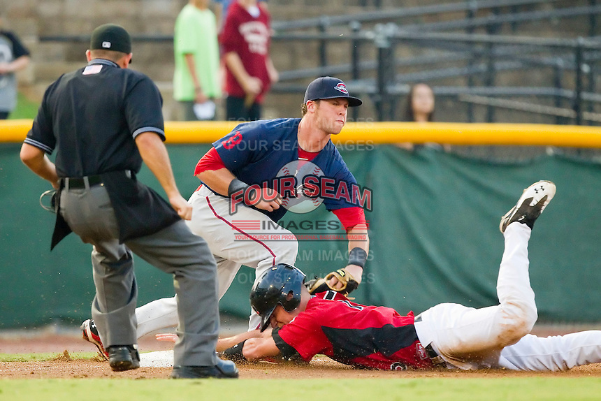 Kellin Deglan #15 of the Hickory Crawdads slides into third base ahead of the tag by David Renfroe #16 of the Greenville Drive at L.P. Frans Stadium on September 3, 2011 in Hickory, North Carolina.  The Crawdads defeated the Drive 3-0.  (Brian Westerholt / Four Seam Images)