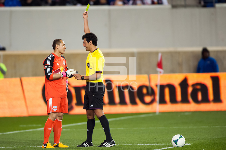 Referee Fotis Bazakos gives a yellow card to New York Red Bulls goalkeeper Luis Robles (31). The New York Red Bulls defeated the New England Revolution 4-1 during a Major League Soccer (MLS) match at Red Bull Arena in Harrison, NJ, on March 20, 2013.