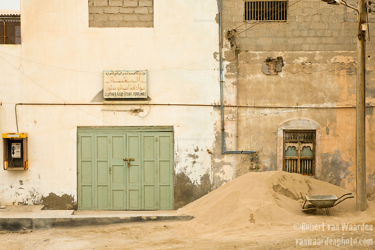 A wheelbarrow and abandoned buildings in Mirbat, Oman.