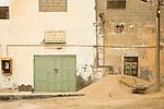 A wheelbarrow and abandoned buildings in Mirbat, Oman.
