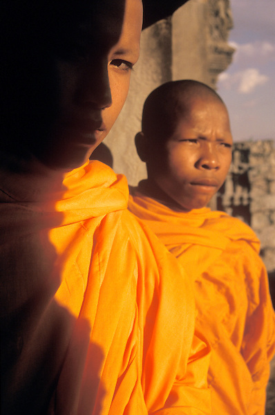 Two young Buddhist monks in a window at Angkor Wat Temple. A Buddhist temple built in 1186 by King Jayavarman VII.