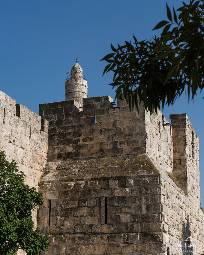 The city wall of Jerusalem with the minaret of the Tower of David or the Citadel in the background. The Old City of Jerusalem and its Walls is a UNESCO World Heritage Site.