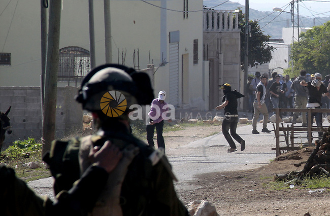 Palestinian protesters throw stones at Israeli soldiers during clashes of the weekly protest against the Jewish settlement of Qadumem, at Kufr Qaddum village near Nablus, West Bank, 26 April 2013. According to reports, 16 Palestinians were wounded in the clashes. Photo by Nedal Eshtayah