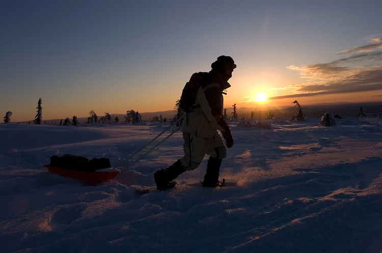 A hiker uses snowshoes to pull a pulk sled across Tolovana Hot Springs dome, north of Fairbanks, in Alaska's interior as the noontime sun reaches its highest point above the horizon.