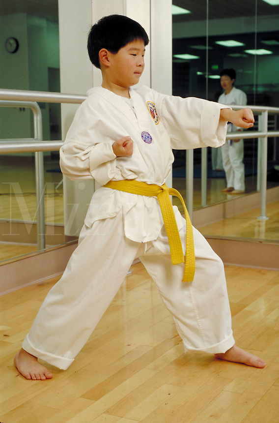 CHINESE-AMERICAN BOY PRACTICING A STANCE FROM MARTIAL ARTS. AIKIDO STUDENT. SAN FRANCISCO CALIFORNIA USA.