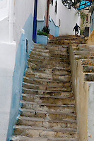 Medina, Tangier, Morocco pictured on December 18, 2009. A small figure climbs a long stone staircase with blue and white painted walls in a corner of the old town. Tangier, the 'White City', gateway to North Africa, a port on the Straits of Gibraltar where the Meditaerranean meets the Atlantic is an ancient city where many cultures, Phoenicians, Berbers, Portuguese and Spaniards have all left their mark. With its medina, palace and position overlooking two seas the city is now being developed as a tourist attraction and modern port. Picture by Manuel Cohen