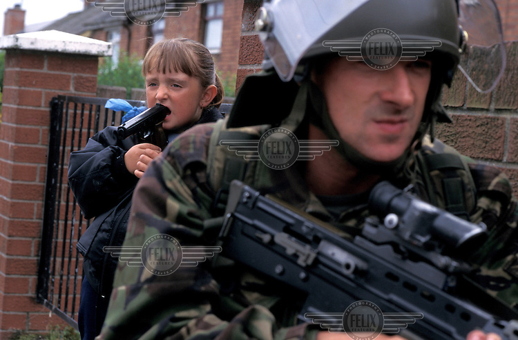 A Catholic girl plays with a toy gun in her mouth next to a patrolling British soldier.