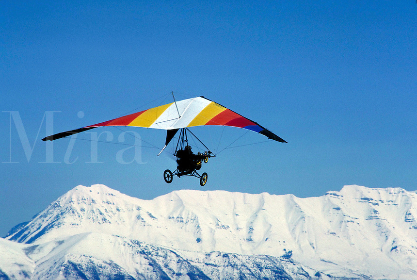 Hanglider converted into an ultralight aircraft in a clear blue sky above Cedar Valley Airport. sports, aviation. Mount Timpanogos in the background. Connotations - Freedom, daring, bravado. Utah, Cedar Valley.