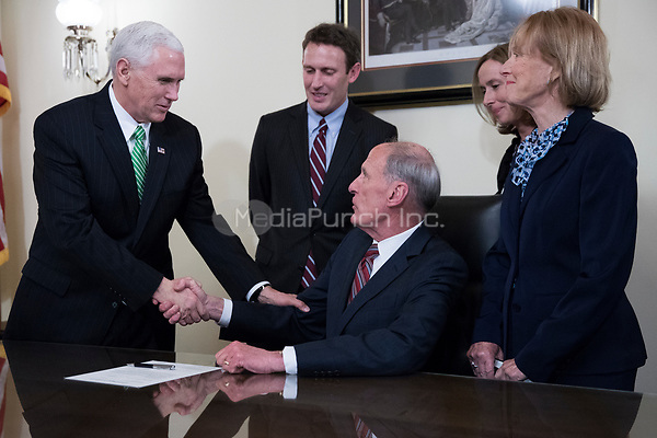 Director of National Intelligence Dan Coats (C), with his wife Marsha Coats (R) and family members, shakes hands with United States Vice President Mike Pence (L)during a swearing in ceremony in the US Capitol in Washington, DC, USA, 16 March 2017.<br /> Credit: Shawn Thew / Pool via CNP /MediaPunch